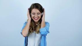 Jonge mooie sexy blondevrouw die in hoofdtelefoons dansen die gelukkig op geïsoleerde witte achtergrond voelen stock videobeelden