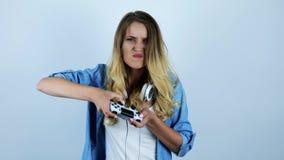 Jonge mooie sexy blondevrouw die met die hoofdtelefoons op haar hals het spelen videospelletje kijken op geïsoleerde witte achter stock videobeelden
