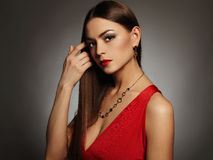 Jonge mooie sexy vrouw Schoonheidsmeisje die juwelen dragen Elegante dame in rode kleding Stock Foto