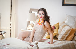 Jonge mooie sexy vrouw in witte korte strakke kleding stellende uitdaging binnen op uitstekend bed Sensueel lang haarbrunette in  Stock Fotografie