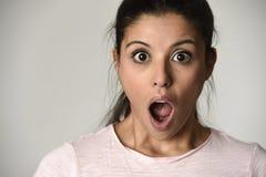 Jonge mooie Spaanse verraste vrouw die in schok en verrassing met geopende mond groot wordt verbaasd Stock Fotografie