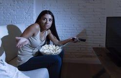 Jonge mooie Spaanse vrouw die thuis op televisie letten die boos en over TV programma's wordt verstoord royalty-vrije stock afbeeldingen