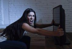 Jonge mooie Spaanse vrouw die thuis op televisie letten die boos en over TV programma's wordt verstoord stock foto's
