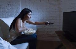 Jonge mooie Spaanse vrouw die thuis op televisie letten die boos en over TV programma's wordt verstoord stock afbeeldingen