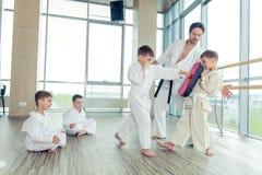 Jonge, mooie, succesvolle multi ethische jonge geitjes in karatepositi stock afbeelding