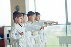 Jonge, mooie, succesvolle multi ethische jonge geitjes in karatepositi royalty-vrije stock afbeeldingen