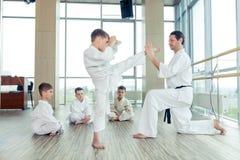 Jonge, mooie, succesvolle multi ethische jonge geitjes in karatepositi stock fotografie
