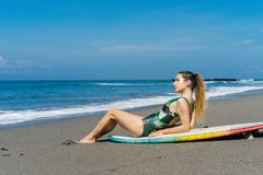 jonge mooie surfer die op surfplank op strand liggen royalty-vrije stock afbeeldingen