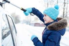 Jonge mooie tiener die witte auto van de wintersneeuw schoonmaken Stock Afbeeldingen