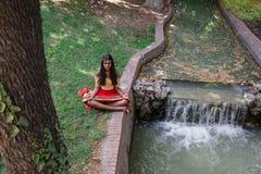 Jonge mooie traditionele Indische vrouw het praktizeren yoga in natu Royalty-vrije Stock Afbeeldingen
