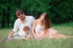 Jonge mooie vader, moeder en weinig peuterzoon tegen groene bomen royalty-vrije stock afbeelding