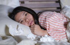 Jonge mooie vermoeide en zieke Aziatische Chinese vrouw die op bed thuis zieken liggen die aan koud griep en temperatuur onwel ge stock fotografie