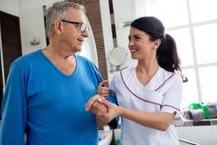 Jonge mooie verpleegstershulp aan de hogere mens bij badkamers Royalty-vrije Stock Afbeelding