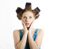 Jonge mooie verraste vrouw met haarkrulspelden Stock Foto's