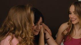 Jonge mooie vrienden die hun geheimen in de slaapkamer toevertrouwen Langzame Motie stock videobeelden