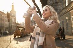 Jonge mooie vrolijke blonde vrouw die foto's met haar uitstekende filmcamera nemen op een zonnige dag bij Rynok-vierkant in Lviv stock foto's