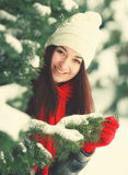 Jonge mooie vrouw achter sneeuw behandelde pijnboom stock afbeelding