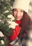 Jonge mooie vrouw achter sneeuw behandelde pijnboom royalty-vrije stock fotografie