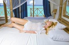 Jonge mooie vrouw in bed met oceaan achter venster Royalty-vrije Stock Fotografie