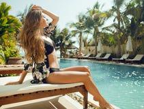 Jonge mooie vrouw bij zwembad die binnen ontspannen Royalty-vrije Stock Fotografie