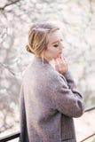 Jonge mooie vrouw dichtbij bomen in bloesem in de lente Stock Foto's