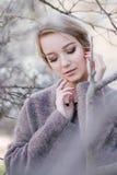 Jonge mooie vrouw dichtbij bomen in bloesem in de lente Verbindende haarstijl Stock Afbeelding