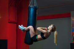 Jonge mooie vrouw die abs training functionele crossfit opleiding op ponsenzak doen Sterk spier sportief klaar meisje stock foto
