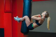 Jonge mooie vrouw die abs training functionele crossfit opleiding op ponsenzak doen Sterk spier sportief klaar meisje stock afbeeldingen
