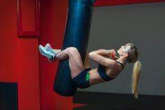 Jonge mooie vrouw die abs training functionele crossfit opleiding op ponsenzak doen Sterk spier sportief klaar meisje royalty-vrije stock foto