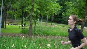 Jonge mooie vrouw die alleen in park bij zomeratleet lopen die Langzame motie opleiden stock footage