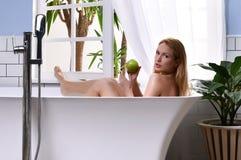 Jonge mooie vrouw die in badkuip liggen en bad nemen dichtbij open badkamersvenster Stock Afbeeldingen