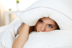 Jonge mooie vrouw die in bed liggen die met slapeloosheid lijden stock afbeelding