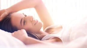 Jonge mooie vrouw die in bed thuis liggen Stock Foto