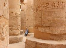 Jonge mooie vrouw die beelden nemen tussen de kolommen van de hypostyle zaal van de tempel van Karnak in Luxor, Egypte royalty-vrije stock foto's