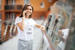 Jonge mooie vrouw die bij cellulaire telefoonvrouw spreken die een gesprek hebben bij smartphone, stad bij zonsondergang op de ac Stock Foto's