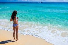 Jonge mooie vrouw die bij de tropische oceaan genieten van Schitterend g Royalty-vrije Stock Afbeeldingen