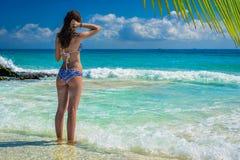 Jonge mooie vrouw die bij de tropische oceaan genieten van Schitterend g Stock Fotografie