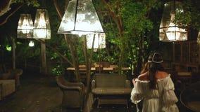 Jonge mooie vrouw die bij nacht in een koffie dansen Witte lampen en houten en rieten meubilair Ontspan en onbezorgd concept stock footage