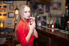 Jonge mooie vrouw die coctails bij de bar drinken Stock Foto's