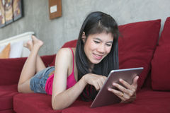 Jonge mooie vrouw die computertablet op rode bank gebruiken Royalty-vrije Stock Afbeeldingen