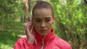 Jonge mooie vrouw die in de herfstpark lopen en aan muziek met hoofdtelefoons luisteren stock footage