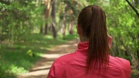 Jonge mooie vrouw die in de herfstpark lopen en aan muziek met hoofdtelefoons luisteren stock videobeelden