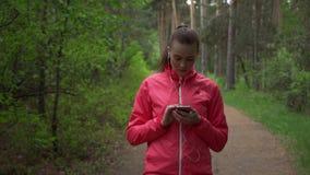 Jonge mooie vrouw die in de herfstpark lopen en aan muziek met hoofdtelefoons luisteren stock video