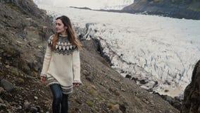 Jonge mooie vrouw die de toneelplaatsen in IJsland onderzoeken wandeling in bergen dichtbij de Vatnajokull-gletsjerslagune stock videobeelden