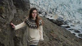 Jonge mooie vrouw die door de rotsen lopen, die in de bergen dichtbij de Vatnajokull-gletsjerslagune wandelen in IJsland stock footage