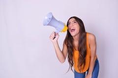 Jonge mooie vrouw die door een megafoon schreeuwen Royalty-vrije Stock Afbeeldingen