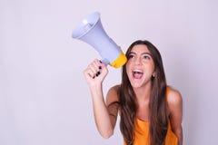 Jonge mooie vrouw die door een megafoon schreeuwen Royalty-vrije Stock Foto