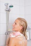Jonge mooie vrouw die in douche met spons nemen Stock Foto