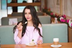 Jonge mooie vrouw die een dessert in een koffie eten stock afbeeldingen