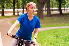 Jonge mooie vrouw die een fiets in park berijden Actieve mensen outdoors stock afbeelding